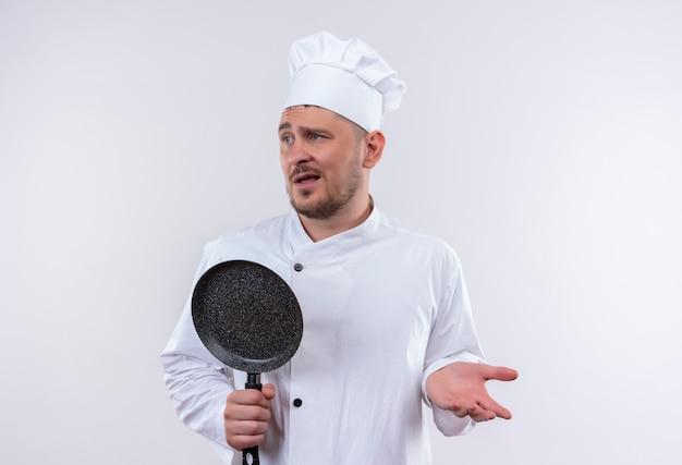 Смущенный молодой красивый повар в униформе шеф-повара держит сковороду, показывая пустую руку и смотрит в сторону, изолированную на белой стене