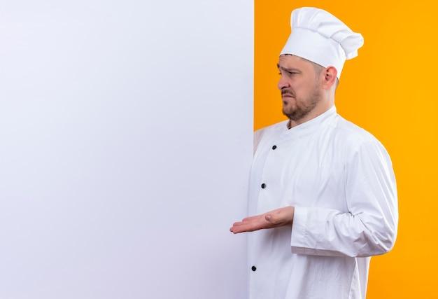 白い壁の後ろに立つシェフの制服を着た若いハンサムなコックが混乱し、コピースペースのあるオレンジ色の壁に手でそれを指している