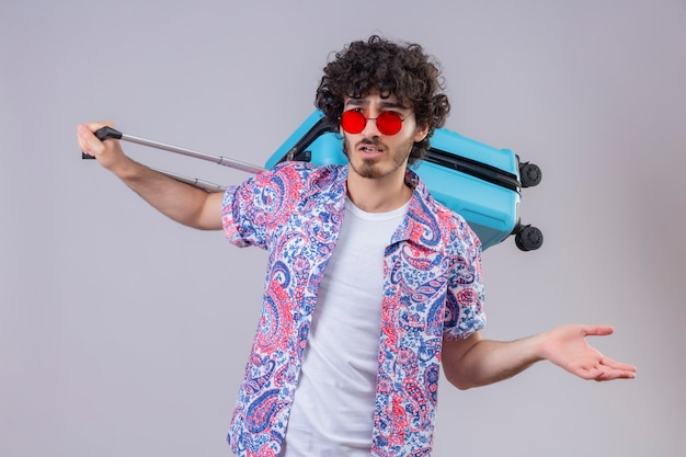 Uomo giovane viaggiatore riccio bello confuso indossando occhiali da sole tenendo la valigia sulla schiena e mostrando la mano vuota su uno spazio bianco isolato