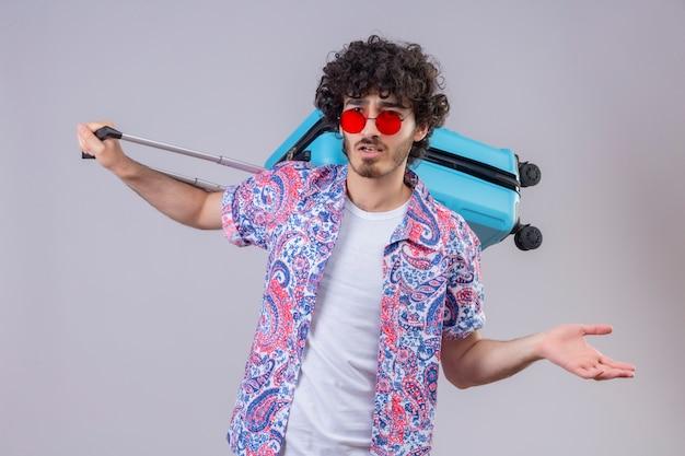 彼の背中にスーツケースを保持し、孤立した白いスペースに空の手を示しているサングラスを身に着けている混乱した若いハンサムな巻き毛の旅行者の男