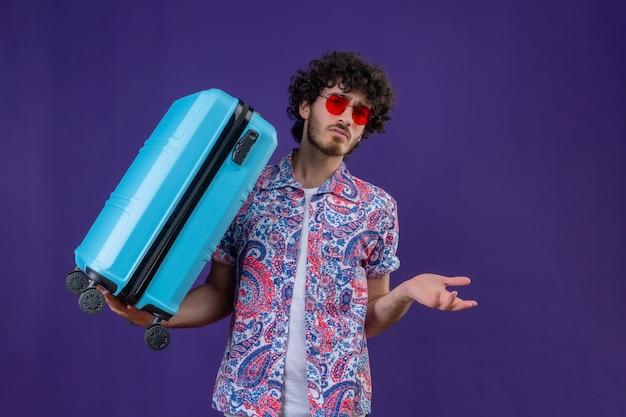 コピースペースと孤立した紫色のスペースに空の手を示すスーツケースを保持しているサングラスを身に着けている混乱した若いハンサムな巻き毛の旅行者の男