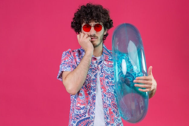 복사 공간이 격리 된 보라색 공간에 턱에 손으로 수영 반지를 들고 선글라스를 착용하는 혼란 스 러 워 젊은 잘 생긴 곱슬 여행자 남자