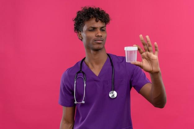 Un confuso giovane bello di carnagione scura medico con i capelli ricci che indossa l'uniforme viola con uno stetoscopio guardando il barattolo di plastica medica