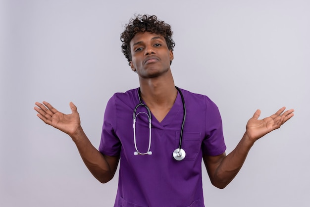 A confused young handsome dark-skinned doctor with curly hair wearing violet uniform with stethoscope opening his hands not know what to do