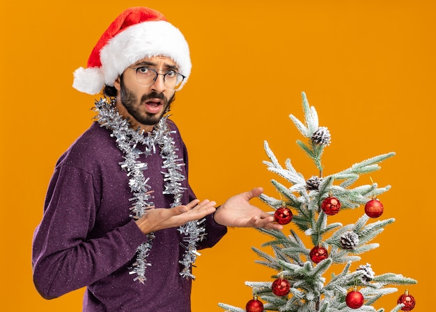 Confused young handsome guy standing nearby christmas tree wearing christmas hat with garland on neck holding and points at tree isolated on orange background