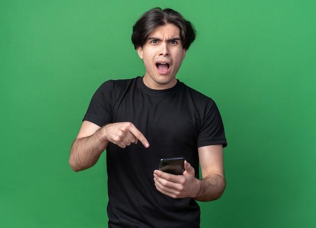 緑の壁に隔離された電話を保持し、黒のtシャツを着て混乱している若いハンサムな男