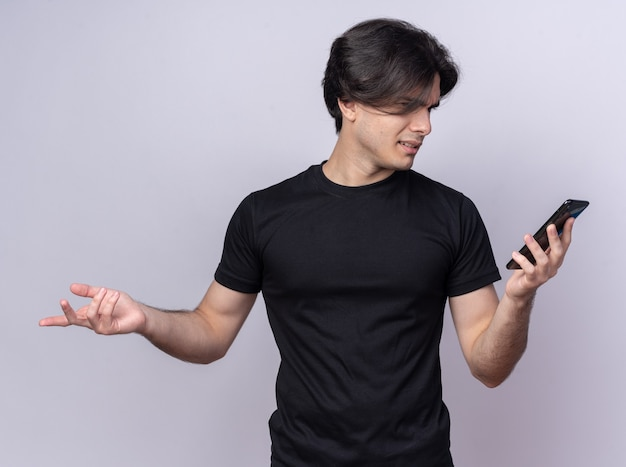 Confused young handsome guy wearing black t-shirt holding and looking at phone spreading hand isolated on white wall
