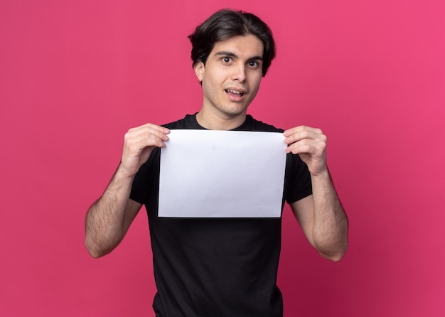 Confused young handsome guy wearing black t-shirt holding paper isolated on pink wall