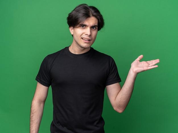 복사 공간이 녹색 벽에 고립 된 측면에서 손으로 검은 티셔츠 포인트를 입고 혼란 젊은 잘 생긴 남자