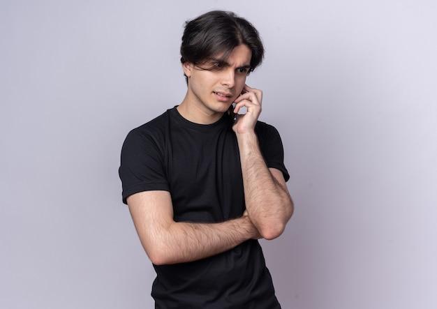 검은 티셔츠를 입고 혼란 스 러 워 젊은 잘 생긴 남자가 흰 벽에 고립 된 전화에 말한다