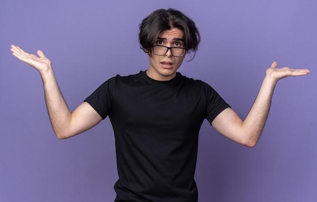 보라색 벽에 고립 된 손을 확산 검은 티셔츠를 입고 혼란 젊은 잘 생긴 남자