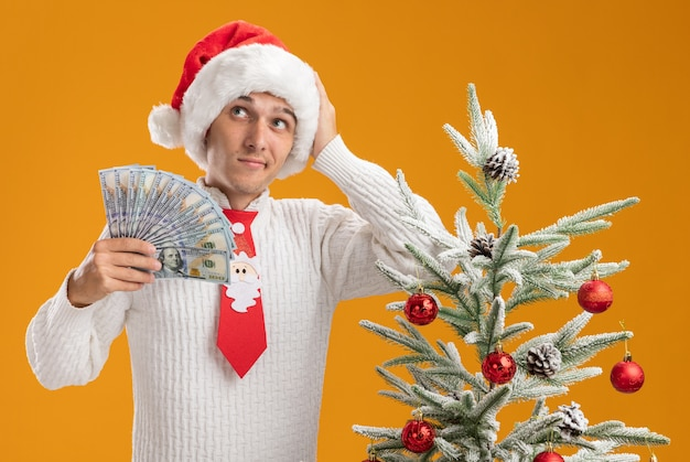 Confused young handsome guy wearing christmas hat and santa claus tie standing near decorated christmas tree holding money keeping hand on head looking at side isolated on orange wall