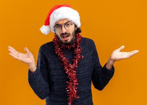 オレンジ色の背景で隔離の手を広げて首に花輪とクリスマス帽子をかぶって混乱した若いハンサムな男