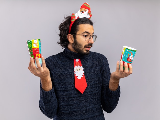Confused young handsome guy wearing christmas tie with hair hoop holding and looking at christmas cups isolated on white background