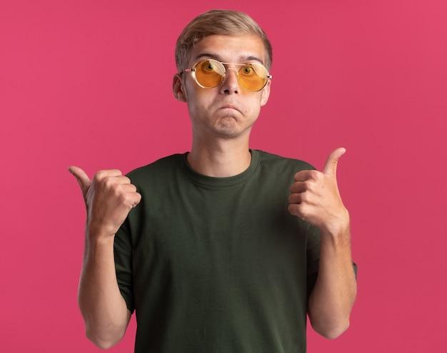 Смущенный молодой красивый парень в зеленой рубашке и очках указывает на разные стороны, изолированные на розовой стене с копией пространства