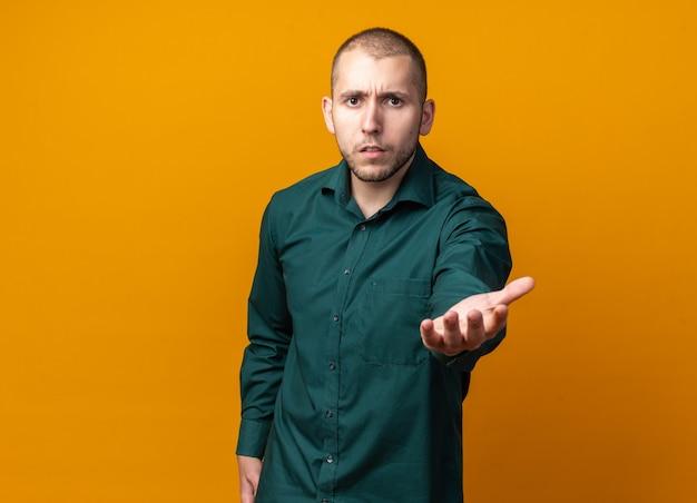 녹색 셔츠를 입고 손을 뻗어 혼란스러운 젊은 잘생긴 남자