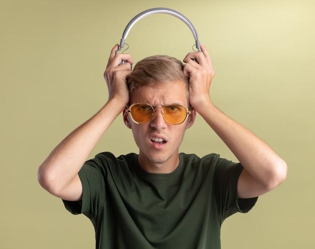 オリーブグリーンの壁で隔離の頭にヘッドフォンを保持しているメガネと緑のシャツを着て混乱している若いハンサムな男
