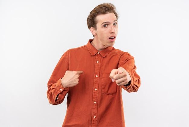 빨간 셔츠를 입은 혼란스러운 젊은 미남이 몸짓을 보여주는 자신을 가리킵니다