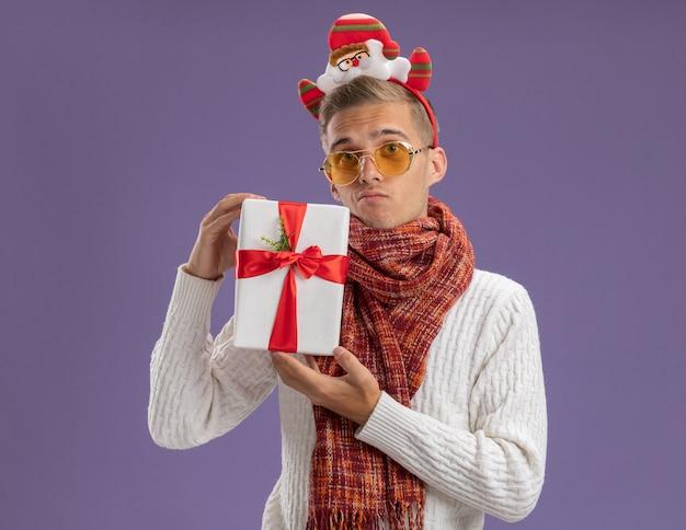 サンタクロースのヘッドバンドと紫色の背景で隔離のカメラを見てギフトパックを保持しているスカーフを身に着けている混乱した若いハンサムな男