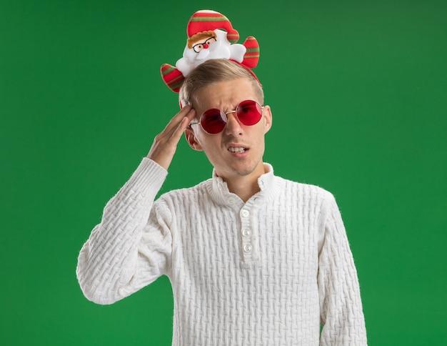 緑の背景で隔離の頭に触れる側を見て眼鏡とサンタクロースのヘッドバンドを身に着けている混乱した若いハンサムな男
