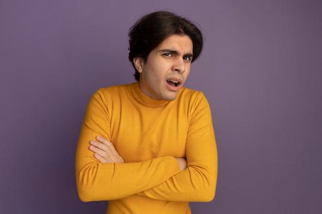 보라색 벽에 고립 된 손을 건너 노란색 터틀넥 스웨터를 입고 혼란 젊은 잘 생긴 남자
