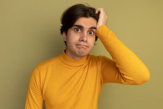 Confuso giovane bel ragazzo indossa maglione dolcevita giallo mettendo la mano sul tempio isolato sulla parete verde oliva