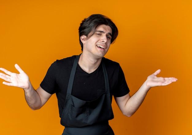 제복을 입은 혼란 스 러 워 젊은 잘 생긴 남성 이발사 오렌지 벽에 고립 된 손을 확산
