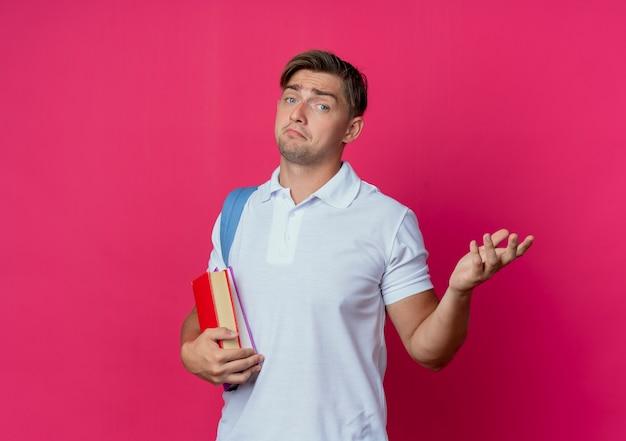 Confuso giovane studente maschio bello che indossa la borsa posteriore che tiene i libri e diffonde la mano isolata sulla parete rosa