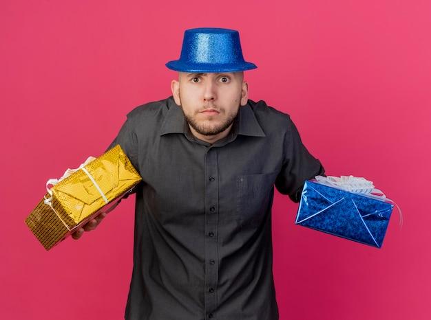 선물 팩을 들고 파티 모자를 쓰고 혼란 스 러 워 젊은 잘 생긴 파티 남자는 분홍색 벽에 고립 된 전면을보고