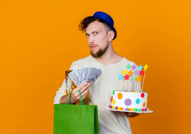 Ragazzo di partito slavo bello confuso che indossa il cappello del partito che tiene il sacchetto di carta dei soldi del contenitore di regalo e torta di compleanno con le stelle che guarda l'obbiettivo isolato su priorità bassa arancione con lo spazio della copia