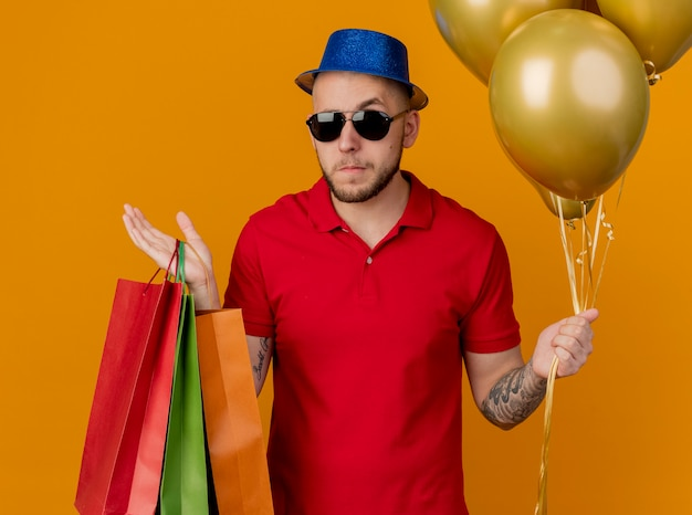Confused young handsome slavic party guy wearing sunglasses and party hat holding balloons and paper bags isolated on orange background