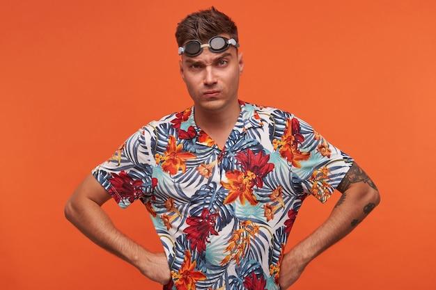 水泳用メガネと花柄のシャツを着て、腰に手を当てて立って、口すぼめ呼吸で眉をひそめ、見ている混乱した若いハンサムなスポーツマン