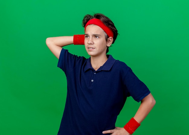 Confused young handsome sporty boy wearing headband and wristbands with dental braces keeping hand on waist and behind head looking straight isolated on green wall with copy space