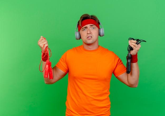 녹색에 고립 된 점프 로프를 들고 머리띠와 팔찌와 헤드폰을 착용하는 혼란 스 러 워 젊은 잘 생긴 스포티 한 남자