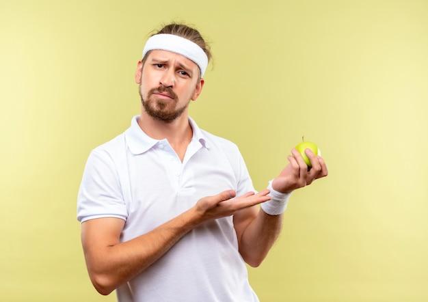 Смущенный молодой красивый спортивный мужчина в головной повязке и браслетах держит яблоко и указывает на него, изолированном на зеленой стене