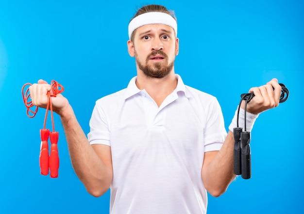 Смущенный молодой красивый спортивный мужчина с повязкой на голову и браслетами, держащими скакалки, изолированные на синей стене
