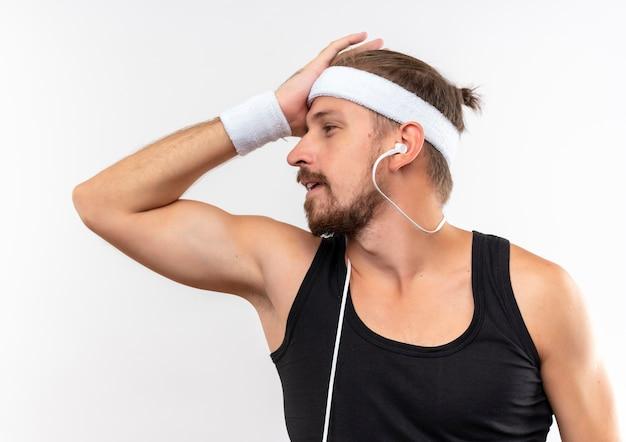 Confuso giovane bell'uomo sportivo che indossa fascia e braccialetti e cuffie mettendo la mano sulla testa guardando il lato isolato sul muro bianco