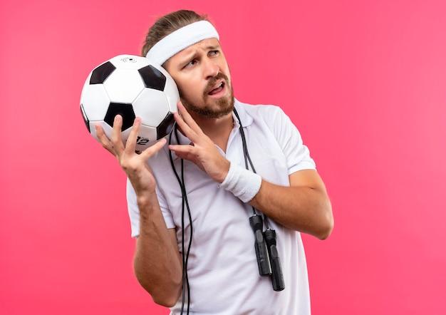 Confuso giovane bell'uomo sportivo che indossa fascia e braccialetti che tengono il pallone da calcio guardando il lato con la corda per saltare intorno al collo isolato sul muro rosa