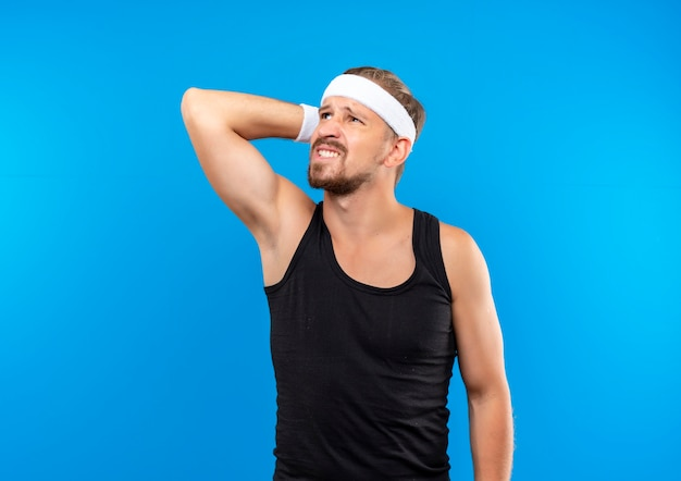 Confuso giovane bello sportivo che indossa fascia e braccialetti mettendo la mano dietro la testa guardando in alto isolato sul muro blu