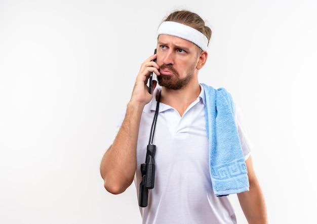 Confuso giovane bell'uomo sportivo che indossa fascia e braccialetti parlando al telefono con asciugamano e corda per saltare sulle spalle guardando il lato isolato sul muro bianco con spazio copia