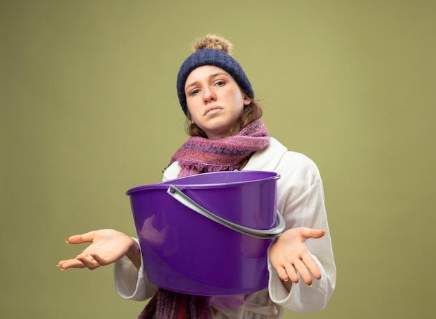 올리브 녹색에 고립 된 플라스틱 양동이 확산 손을 잡고 스카프와 흰 가운과 겨울 모자를 쓰고 혼란 어린 아픈 소녀