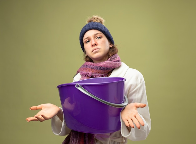 Confused young ill girl wearing white robe and winter hat with scarf holding plastic bucket spreading hands isolated on olive green