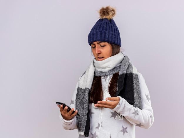 スカーフを持って冬の帽子をかぶって、白で隔離の電話を見て混乱している若い病気の女の子