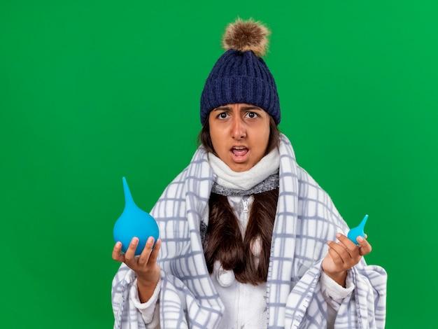 녹색 배경에 고립 된 관장을 들고 스카프와 겨울 모자를 쓰고 혼란 어린 아픈 소녀