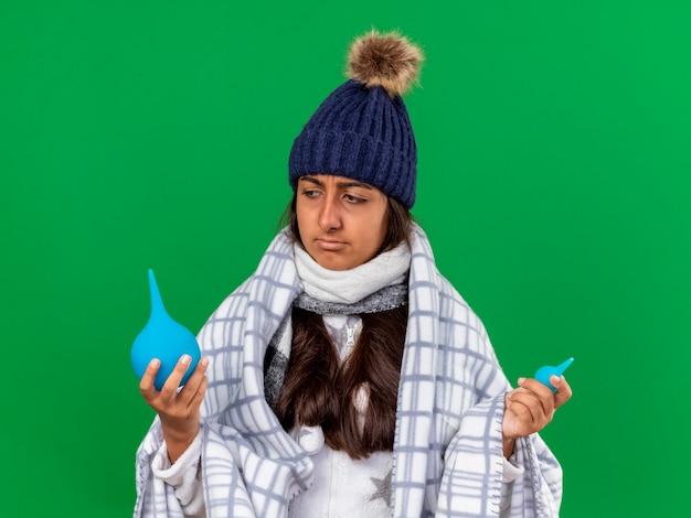 Confused young ill girl wearing winter hat with scarf holding and looking at enemas isolated on green background