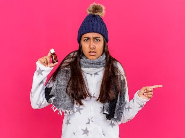 Confusa giovane ragazza malata che indossa un cappello invernale con sciarpa tenendo la medicina in bottiglia di vetro punti a lato isolato su sfondo rosa con spazio di copia