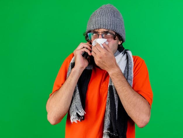 복사 공간이 녹색 벽에 고립 된 측면을보고 코를 닦아 전화로 얘기 안경 겨울 모자와 스카프를 착용하는 혼란 젊은 아픈 남자