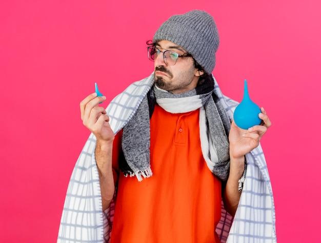 분홍색 벽에 고립 된 작은 하나를보고 격자 무늬 지주 관장에 싸여 안경 겨울 모자와 스카프를 착용하는 혼란 젊은 아픈 남자