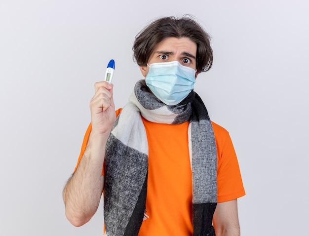 스카프와 흰색 배경에 고립 된 온도계를 들고 의료 마스크를 쓰고 혼란 된 젊은 아픈 남자