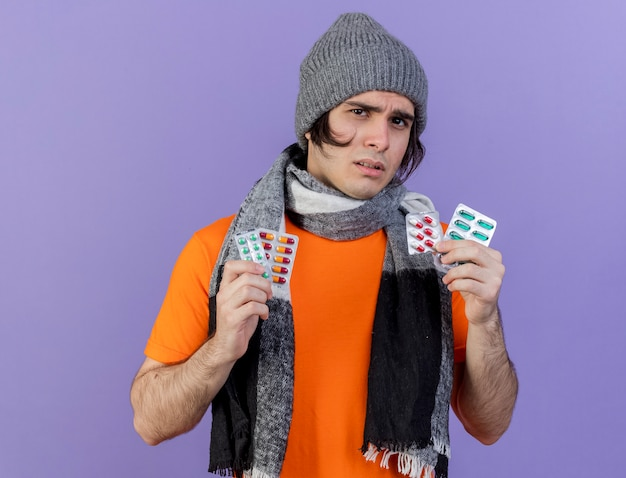Confused young ill man wearing winter hat with scarf holding pills isolated on purple background